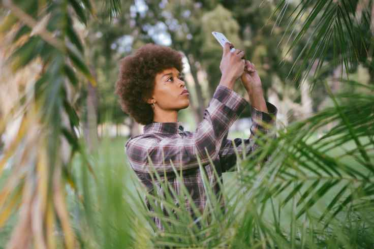 photo of woman taking picture of plants